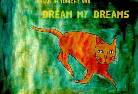 Gemalte orangene Katze läuft über gruenen Hintergrund