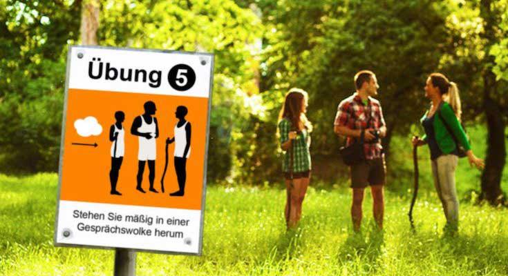 Trimm-dich-Anleitung und drei Wanderer auf einer Lichtung